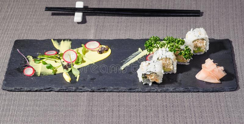 Uramaki rool with cheese and vegetables, japponese cuisine revisited. Served on a rectangular blackboard dish stock images