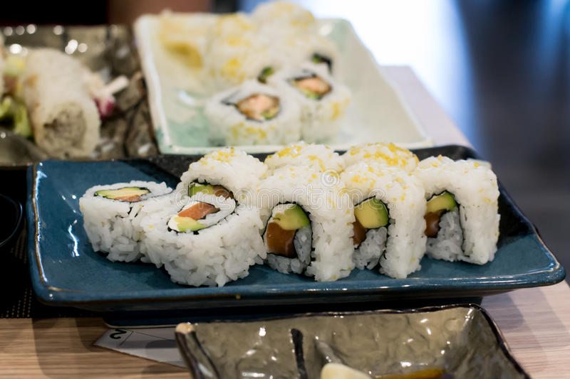 Uramaki sushi rolls with fresh salmon, avocado and philadelphia cheese royalty free stock photos