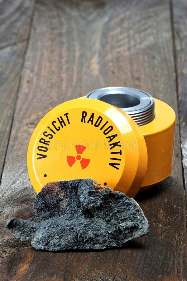 Uraninite. With storage container for radioactive materials stock image