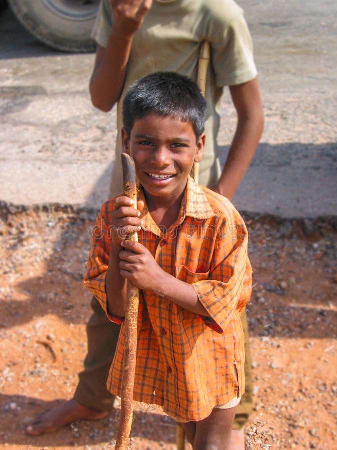 Handicapped Indian Boy. URAVAKONDA, ANDRAH PRADESH, INDIA - DEC 2006: Young handicapped Indian boy supported by a stick smiles while asking for an offering royalty free stock photography