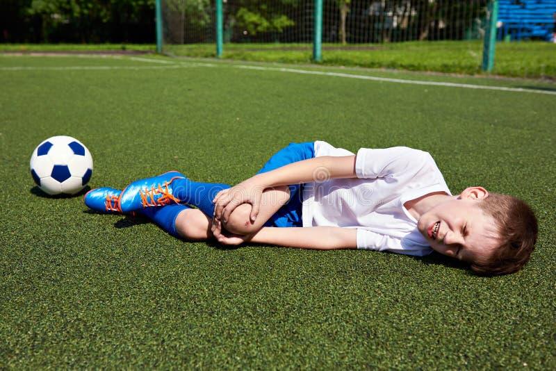 Uraz kolano w chłopiec futbolu na trawie fotografia royalty free