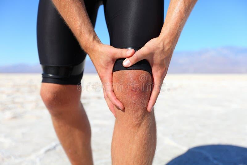 Urazy - sporty biega uraz kolana na mężczyzna zdjęcie royalty free
