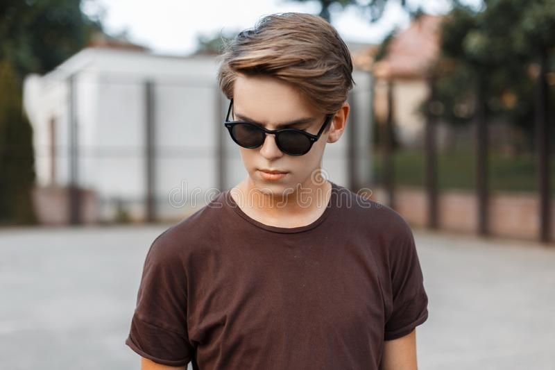 Urban american hipster young man in sunglasses in trendy t-shirt with hairstyle on a modern basketball court outdoors. stock image