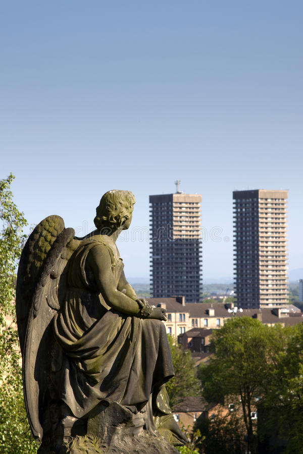 Glasgow Necropolis Graveyard. Glasgow Necropolis burial ground statue of Victorian angel contemplating two modern high rise tower blocks against the skyline royalty free stock images