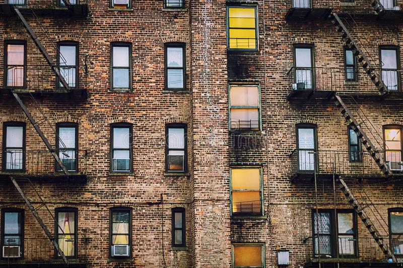 Urban Apartment Building Rear Exterior View`. Urban apartment building rear exterior with windows, fire escapes and air conditioners stock image