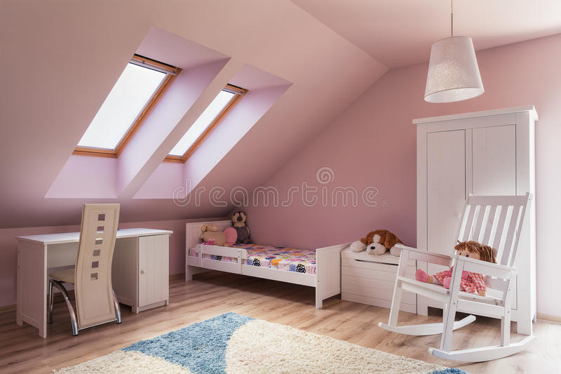 Urban apartment - kids room. Urban apartment - cute pink girl's room on the attic stock images
