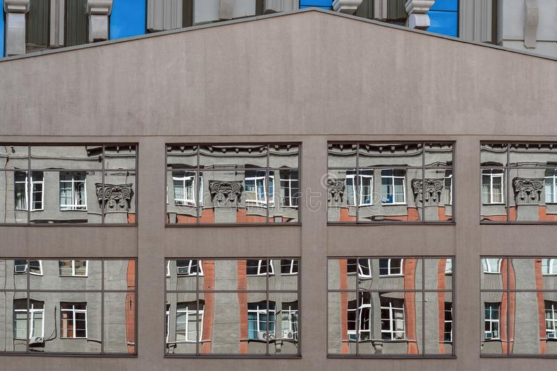 Urban architecture. Distorted reflection of one building in mirrored windows of other. royalty free stock photography