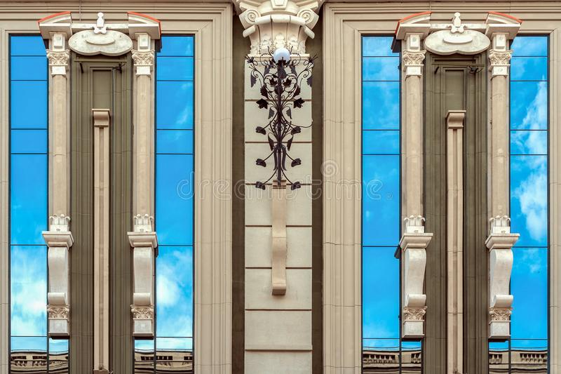 Urban architecture. Vertical mirrored windows of modern building and reflection of blue sky in it. royalty free stock images