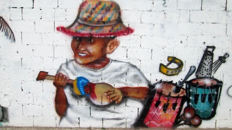 Urban Art in eastern Venezuela. Graffiti located in the sector Caigüire Cumana, Sucre State, Venezuela. It shows a guy playing a typical musical instrument of stock photo