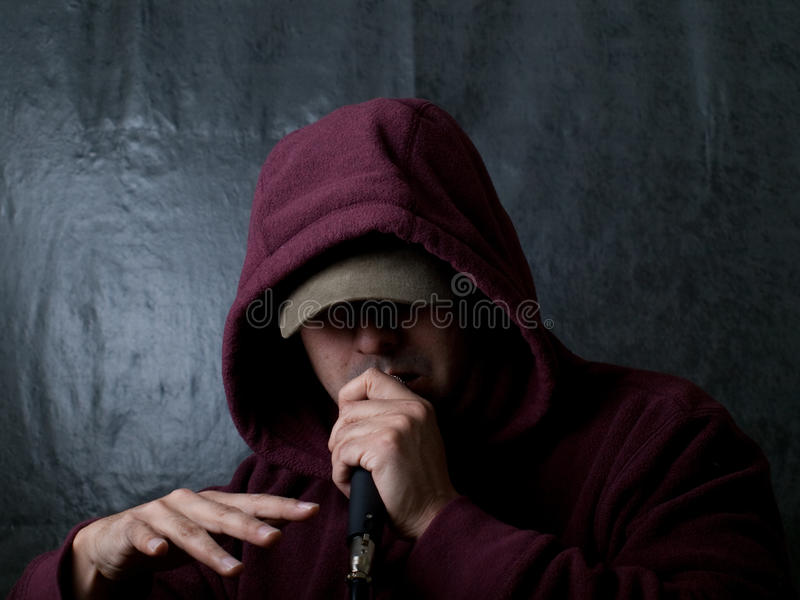 Urban artist - rapper. Rapper wearing hood and singing to a microphone royalty free stock photography
