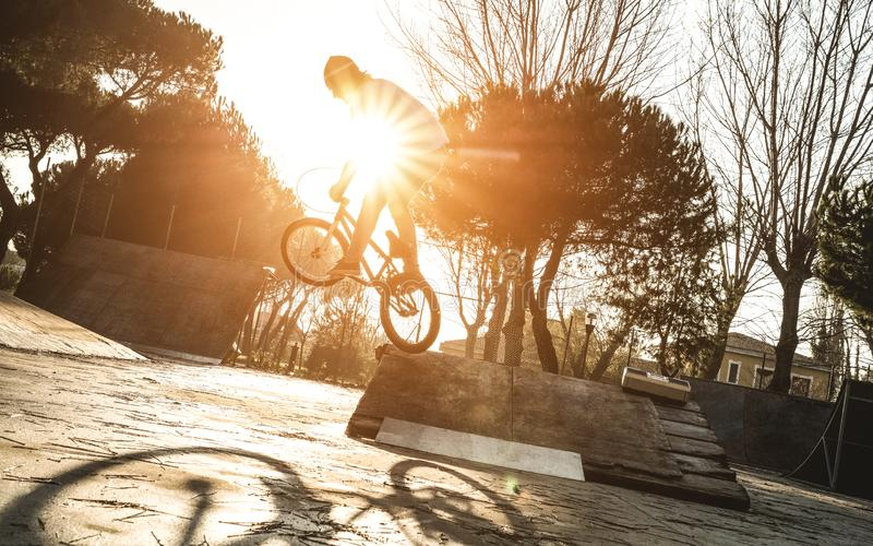 Urban athlete biker performing acrobatic jump at public park - Guy riding bmx bicycle at extreme sport competition stock photography