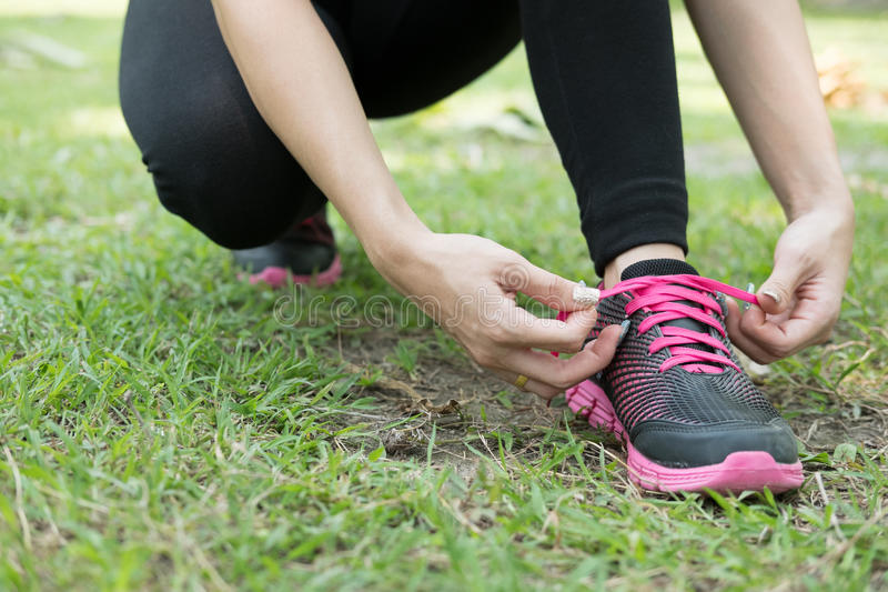 Urban athlete woman tying running shoe laces. Female sport fitness runner getting ready for jogging outdoors on forest path in ci royalty free stock photography