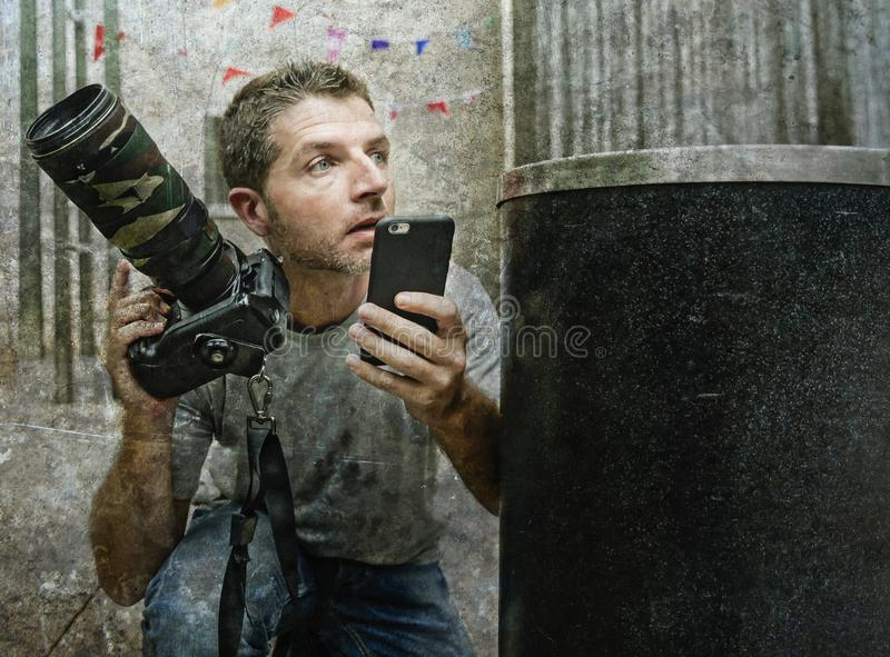 Lifestyle funny portrait of young paparazzi photographer man in action hidden behind city paper basket stalking for shooting excl royalty free stock photo