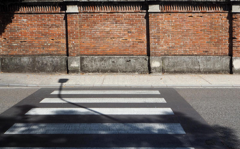 Urban background. Pedestrian crossing and street lamp shadow in front of an old brick wall. royalty free stock photos
