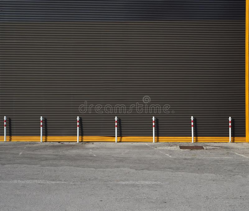 Urban background. red and white poles in front of black metal wall and a road royalty free stock photo