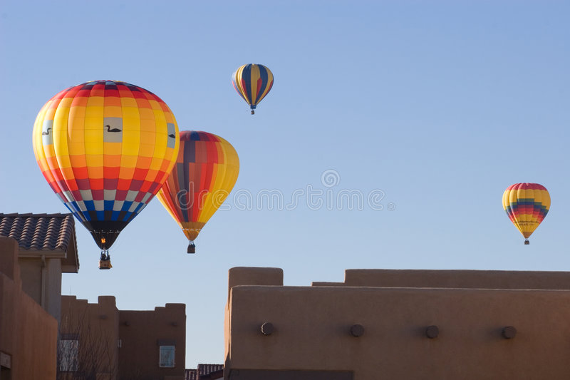 Urban ballooning 2. Four brightly-colored hot air balloons pass closely over the rooftops of adobe houses in Albuquerque, New Mexico against a bright blue winter royalty free stock photos