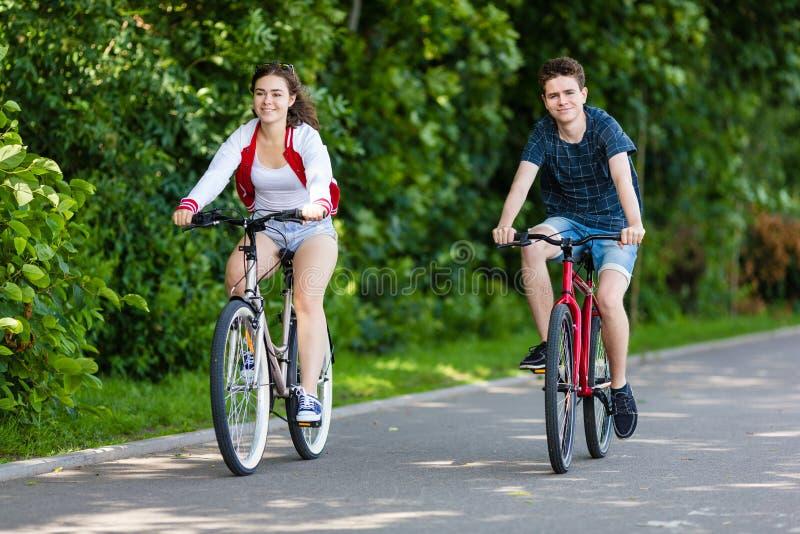 Urban bicycle - teenage girl and boy cycling stock image