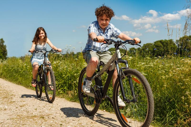 Urban biking - kids riding bikes. Outside royalty free stock photography