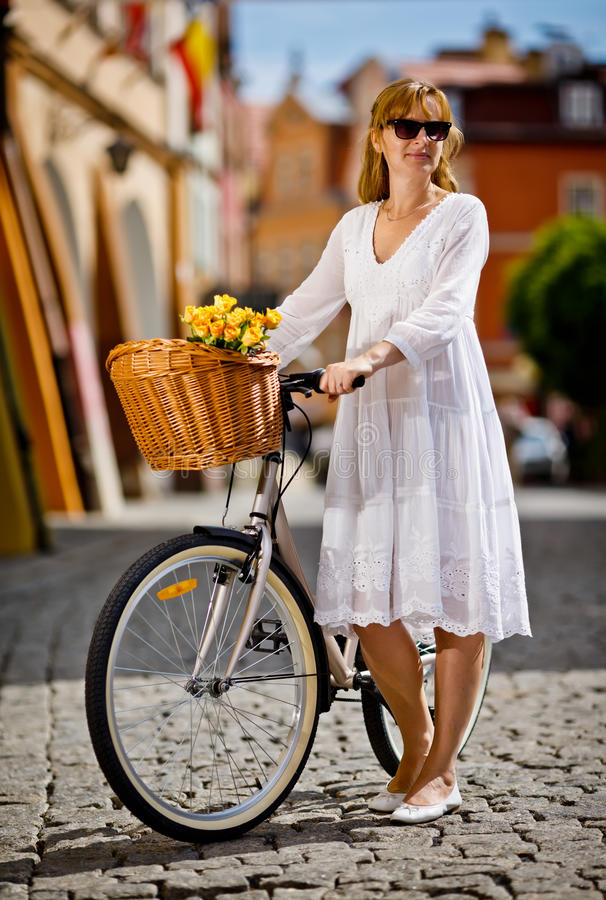 Urban biking - middle-age woman and bike in city royalty free stock photography