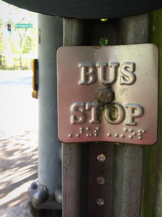 Urban Bus Stop Sign with Braille. Signs, signage, city, language, written, writing, blind, metal, tag, label, transportation, transit, system, public, service stock photography