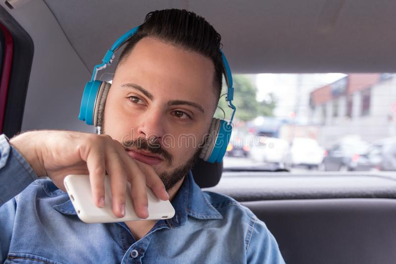 Urban businessman wearing denim shirt on back seat of car listening to music on a smartphone. Concept of aspirations,. Young urban businessman professional royalty free stock images