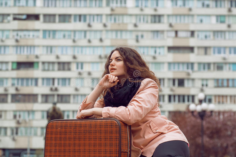 Urban city lifestyle cityscape and young woman with vintage suitcase thinking about life.  stock photos