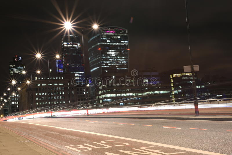 Urban city night shot on London Bridge, Red Bus in Motion, long exposure shot royalty free stock image