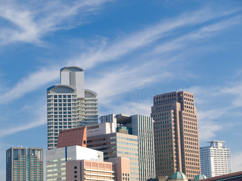 Urban city scene. During the daytime with many tall office buildings in Osaka, Japan with a blue sky and thin white clouds in the background stock photography