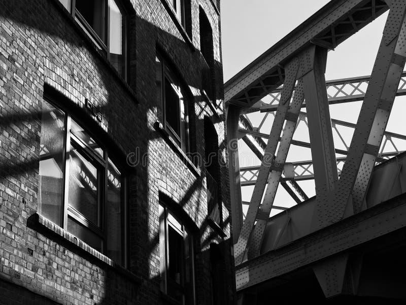Urban City Street Corner: Vintage Train Bridge and Brick Wall Building in London. Black and white image of urban city street corner with vintage train bridge and stock images
