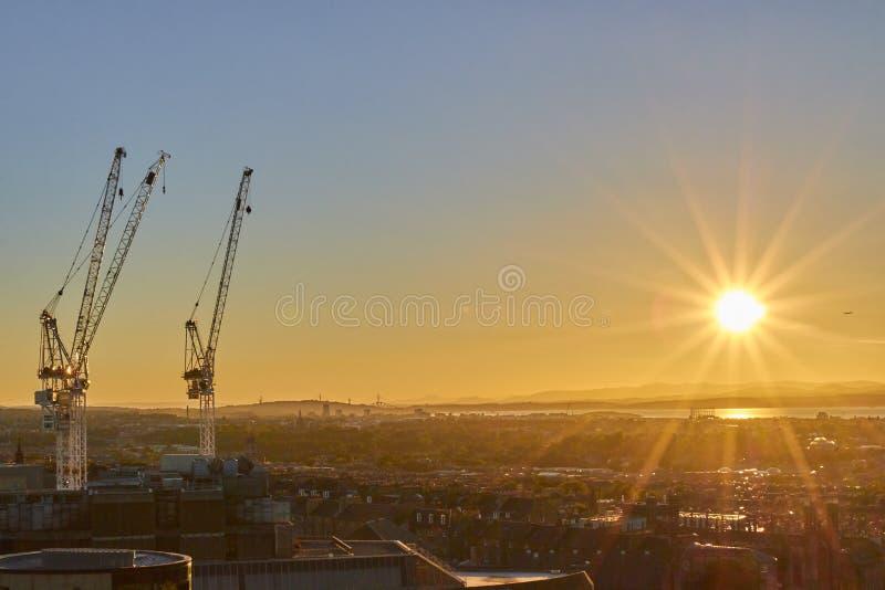 Urban cityscape with cranes in sunset with sun rays, Edinburgh, Scotland, United Kingdom. Urban cityscape with cranes in sunset with sun rays, Edinburgh stock image