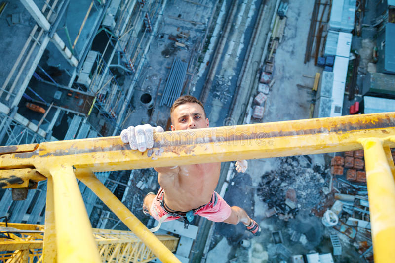 Urban climbing: rock climber hanging on jib of construction crane with one hand. View of construction site below royalty free stock photo