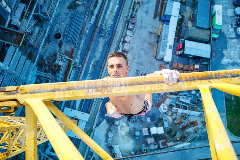 Rock climber hanging on jib of construction crane with one hand. Urban climbing: rock climber hanging on jib of construction crane with one hand, view of royalty free stock photo