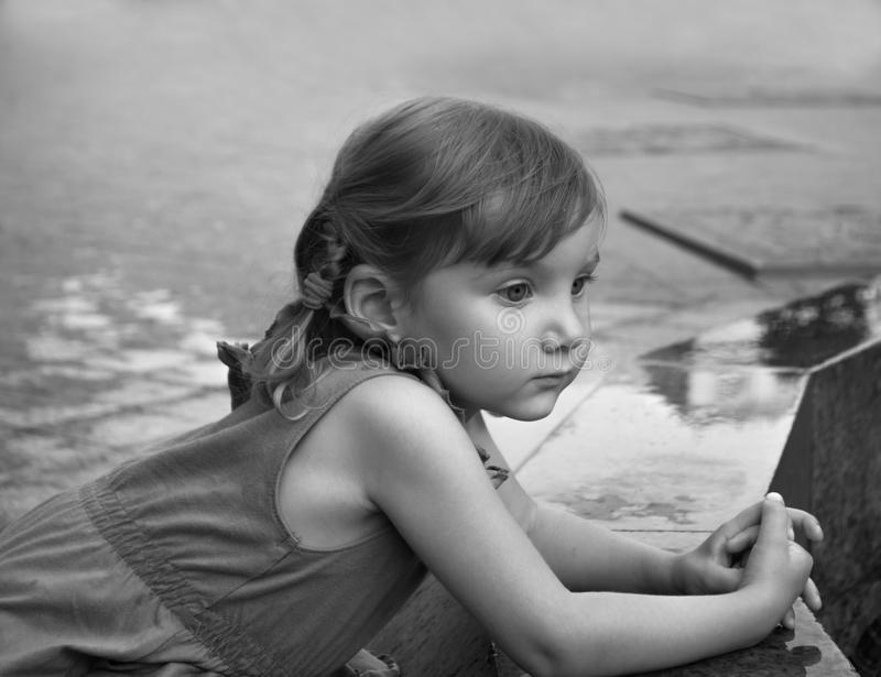 An urban close up serious portrait of a little girl near the granitic parapet wall of a fountain stock photos