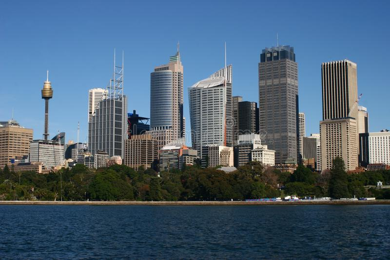 City waterfront coastline with iconic cityscape of Sydney downtown skyline skyscrapers above tree line. Urban coastal shoreline with iconic contemporary high royalty free stock images