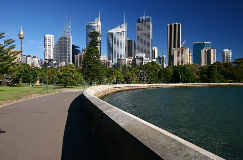 Coastal road along shoreline to city downtown with iconic cityscape of modern skyscrapers and trees on harbor waterfront in Sydney. Urban coastline with iconic stock photography