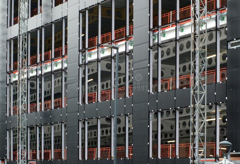 Urban construction site with cladding being fastened to the metal framework of a large commercial development with orange fence. An urban construction site with stock photography