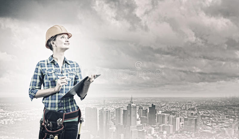Urban construction. Young woman builder with projects in hand stock image