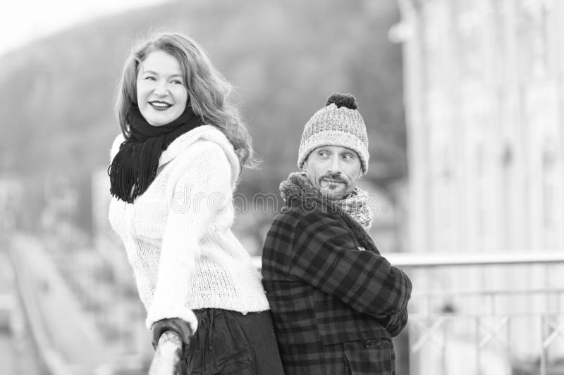 Urban couple on the bridge. Happy couple standing back to back. Men and woman look in one way. Smiling brunet hair woman and happy stock photos