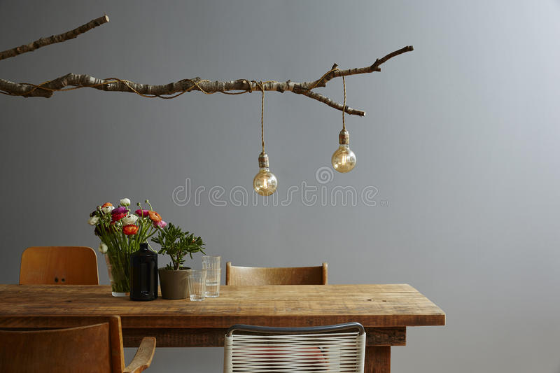 Urban design modern decoration wooden table designer lamp and chair mix. Creative birch branch lamp with bulbs stock photos
