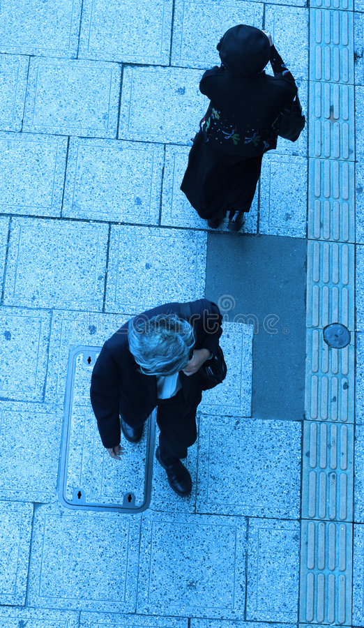 Urban destinies. A man and a woman walking in different directions on a city street-upper blue view royalty free stock images