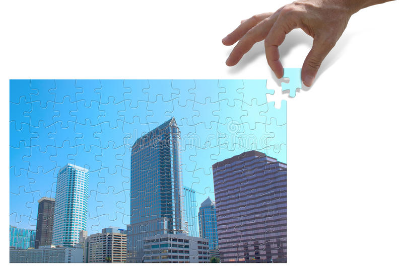 Urban development and city planning concept. Showing a hand putting the last puzzle piece in place of a beautiful city skyline stock photo