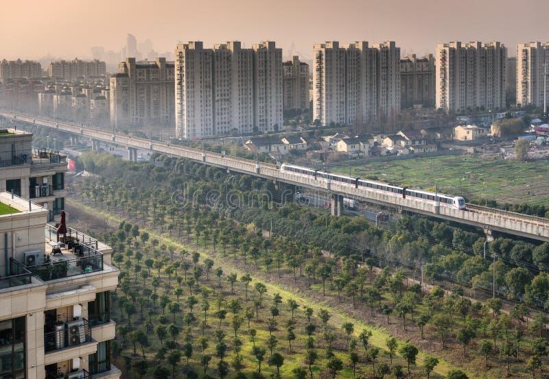 Urban Development Shanghai -Metrolink China. The MetrolinkTrain passing by the fields in the urban area in Shanghai China stock image