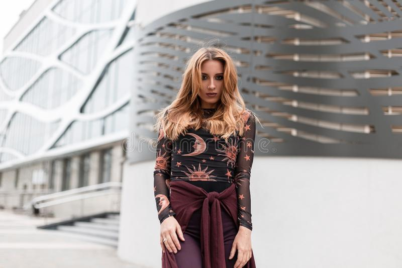 Urban European pretty young woman in vintage trousers with a purple cape in a fashionable blouse with a pattern posing. On the street near the modern building stock photography