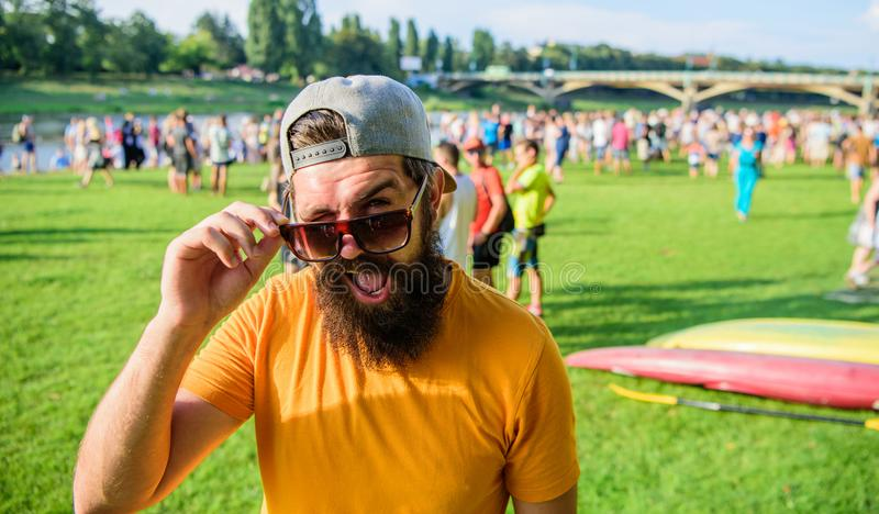 Urban event celebration. Man look through sunglasses sunny day outdoors. Hipster in cap visiting social event picnic stock photo