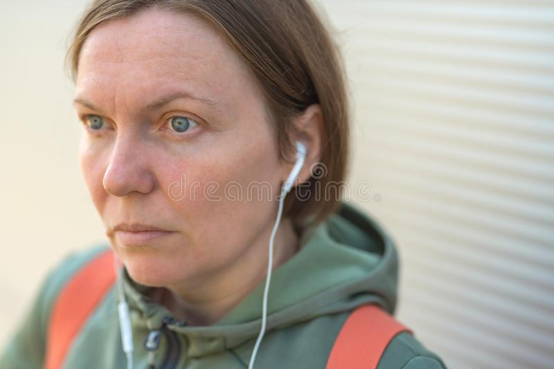 Urban female person listening to music on earphones on street stock images