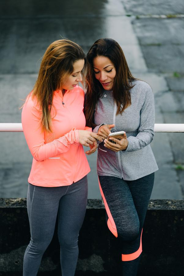 Urban fitness women checking training with smartphone app stock images