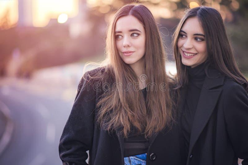 Urban girls walking down the street. Two beautiful girls on the street having a small chat, enjoying a walk stock image