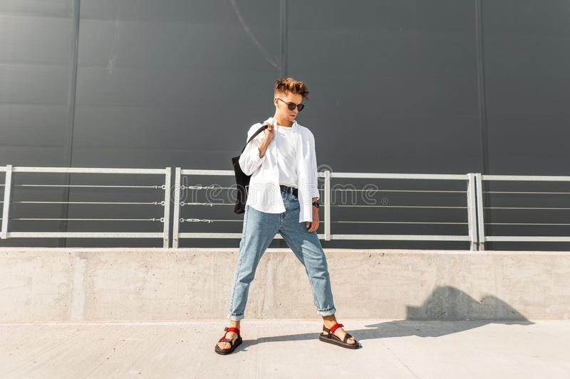 Urban hipster young man in a vintage shirt in blue jeans in red sandals in black sunglasses with a cloth bag is posing. On the street near a gray building stock photo