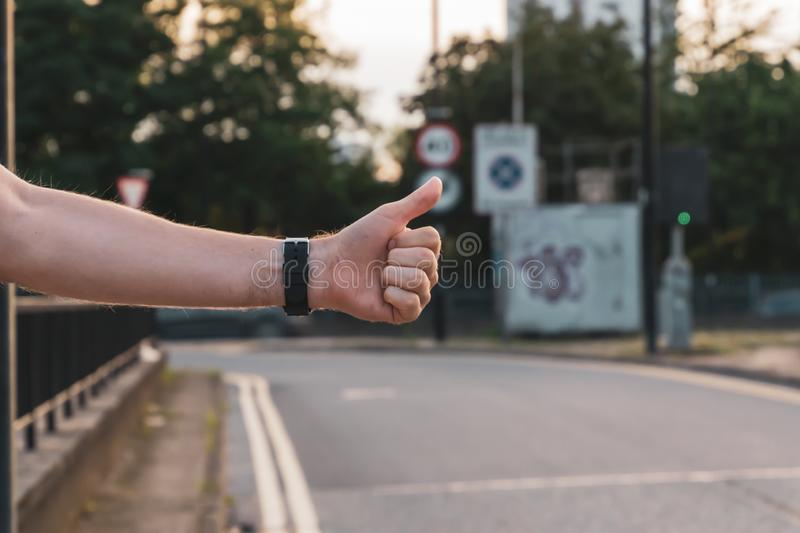Urban hitchhiker in the city trying to catch a taxi cab. The guy is trying to catch a passing car. Hitchiker, adventure, arm, freedom, hand, journey, lifestyle royalty free stock photos