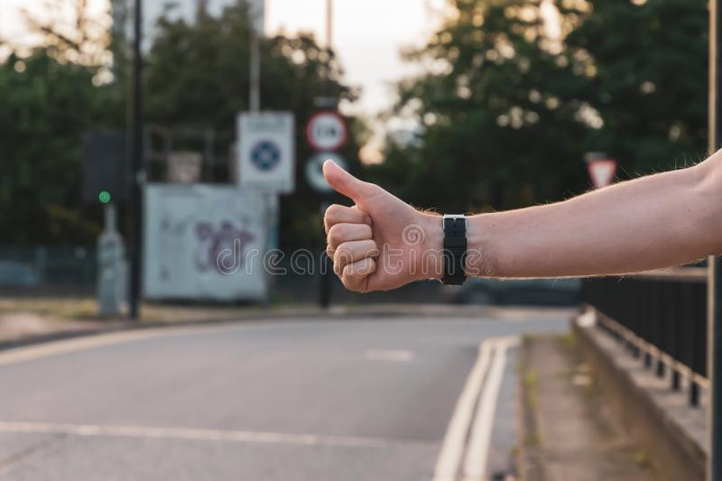 Urban hitchhiker in the city trying to catch a taxi cab. The guy is trying to catch a passing car. Hitchiker, adventure, arm, freedom, hand, journey, lifestyle royalty free stock image